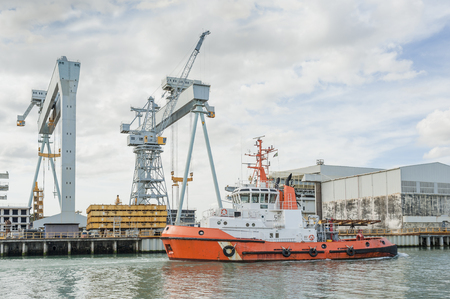 tugboat: Tugboat at work at a shipyard with cranes in the background Stock Photo