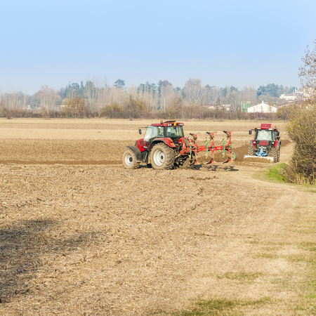 plowing: Agricultural labor, Red Tractor plowing a field