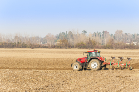 plough land: Agricultural labor, Red Tractor plowing a field