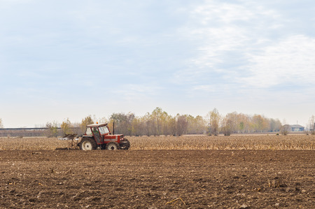 plowing: Tractor plowing a field with a plow. Stock Photo