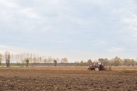 arando: Tractor arando un campo con un arado.