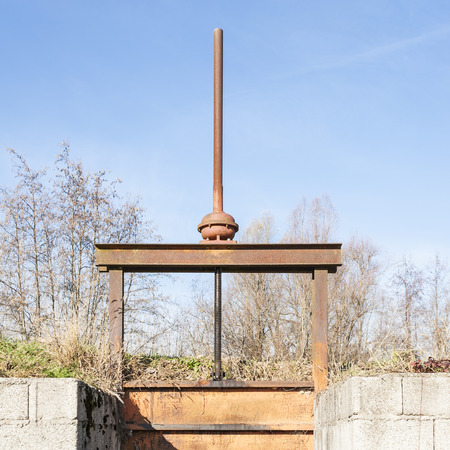 sluice: Irrigation Canal and old and manual Flood gate valve