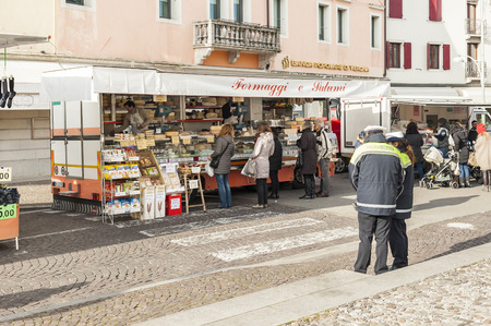 cops: Codroipo,Udine,Italy  - 19 January 2015 :Stand of meats, cheeses and specialty in a market in the North East of Italy. The local cops control sales licenses with discretion.