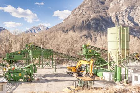 aggregates: Gemona,Udine,Italia - january 16 2016 : Gravel extraction plant.   Machinery and classification according gravel size distribution via conveyor belts.