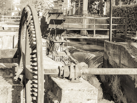 molino de agua: Old iron wheel a watermill. Ruins of a watermill. Foto de archivo
