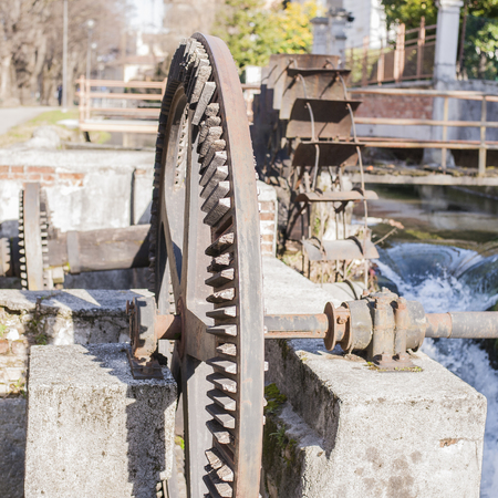 wood turning: Old iron wheel a watermill. Ruins of a watermill. Stock Photo