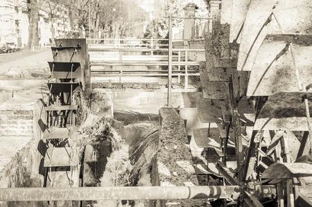 molino de agua: Rueda de hierro viejo molino de agua. Las ruinas de un molino de agua. Efecto de la vendimia.