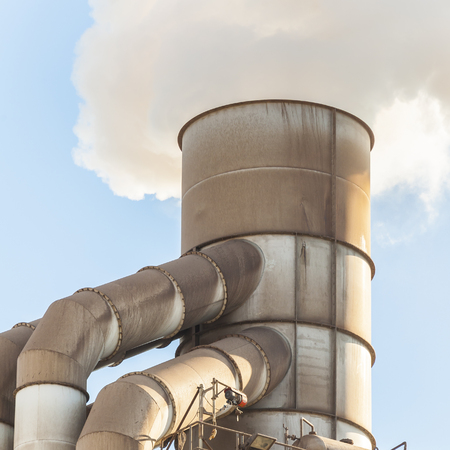 environmental concern: Old smokestack that emits white smoke. Stock Photo