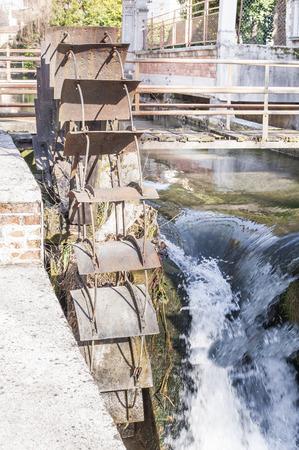 watermill: Old iron wheel a watermill. Ruins of a watermill. Foto de archivo