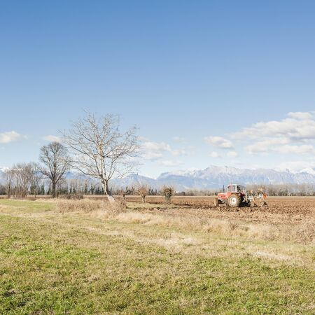 plough machine: Agricultural landscape. With tractor plowing a field. The mountains in the background.