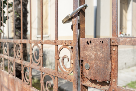 safekeeping: Rusty metal gate closed with padlock - concept image
