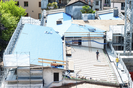 Udine,Italy - April 28 2016 :  Construction site. Construction crew working on the roof sheeting. Editorial