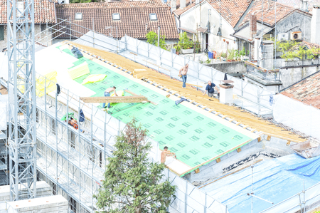 trussing: Udine, Italy - May 3 2016 : Construction crew working on the roof sheeting