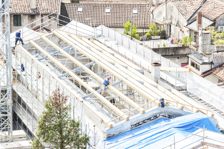 construction crew: Udine,Italy - April 28 2016 :  Construction site. Construction crew working on the roof sheeting. Editorial