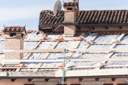 sheeting: Emergency repair of a roof with plastic sheeting. Stock Photo