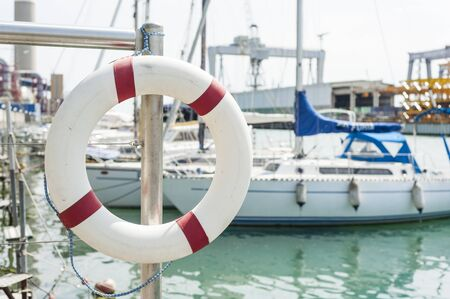 buoy: White life buoy hanging from a railing at the port. Stock Photo
