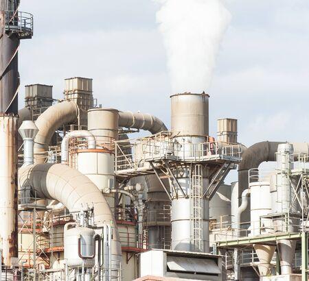 smokestack: Industrial plant of a furniture factory with smoking smokestack,tube,silos.