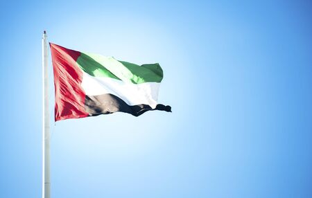 uncluttered: United Arab Emirates flag flying against clean and tranquil sky Stock Photo