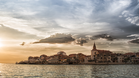 stormy sky: The coast and the promontory of Umag Croatia at sunset with stormy sky