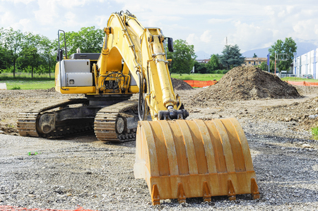 earthmover: Excavator shovel at construction site by building a road.