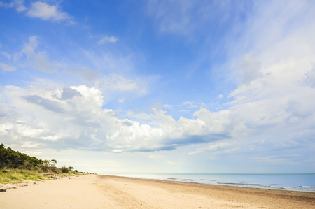 unspoilt: View of beach, vegetation, sea and sky with clouds Stock Photo