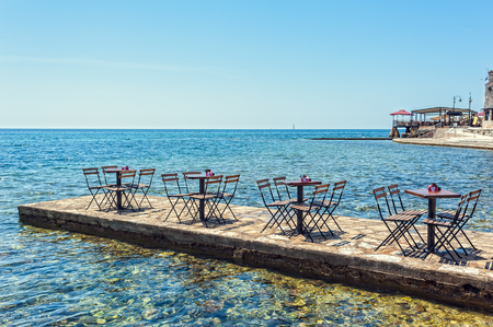 A row of small tables of bars on the pier at sea