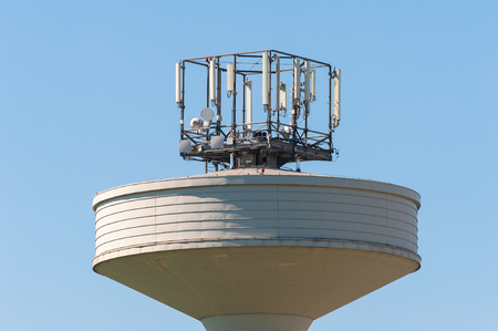 surmounted: Water tank tower surmounted with a telephone repeater antennas against il cielo blu.Copy space Stock Photo