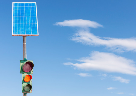 voltaic: Road traffic light powered by electricity generated from a solar panel. Blue sky Stock Photo