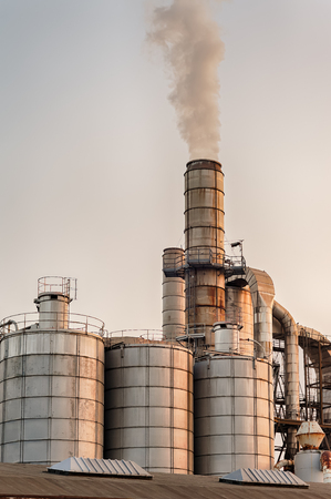 smokestacks: Chemical plant at sunset. Silos and smokestacks of a factory. Stock Photo