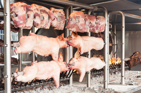 carcasses: Carcasses of pork and other meat prepared on skewer. Cooking on grill and fire. Stock Photo