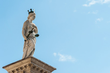 sword act: Statue of Justice, on the background of the sky