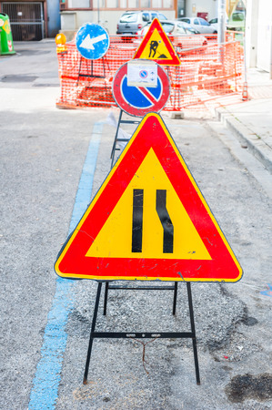 narrowing: Road sign lane narrowing. In the background, blurred a roadworks