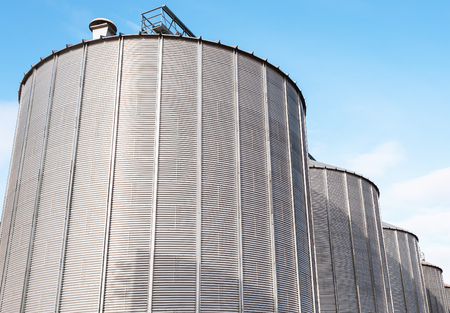 Agricultural Silos. Building Exterior. Storage and drying of grains, wheat, corn, soy, sunflower against the blue sky with white clouds Stock Photo
