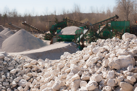 gravel pit: Pile of gravel-rock to be treated. Blurred on background machinery of a gravel pit. Stock Photo