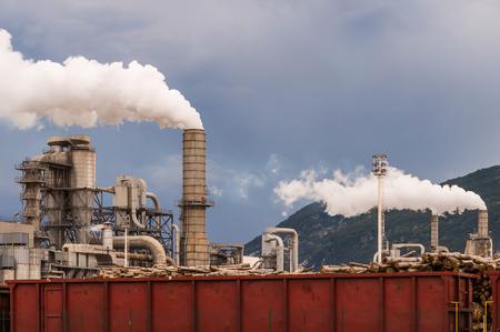 Industrial plant. Smokestacks ,storage tanks and rail wagon. Lumber industry