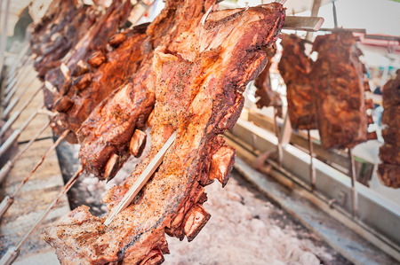 Roasted meat of beef cooked on a vertical grills placed around fire. Asado, traditional barbecue dish in Argentina Standard-Bild