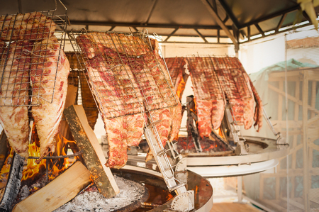 brazier: Asado, traditional barbecue dish in Argentina.  Roasted meat of beef cooked on a vertical grills placed around fire Stock Photo