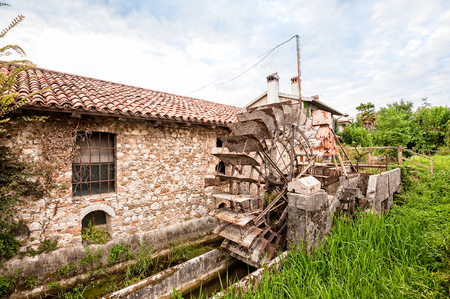 Old water mill with iron water wheel.