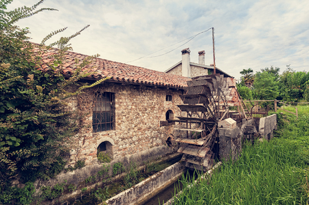 Old water mill with iron water wheel. Photo in vintage style. Stock Photo