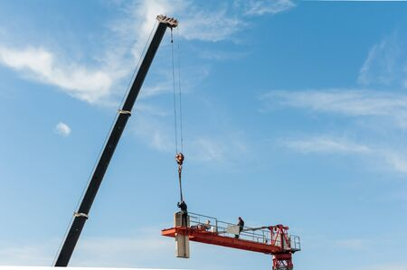 Unrecognizable technicians involved in the assembly of a construction crane. Standard-Bild