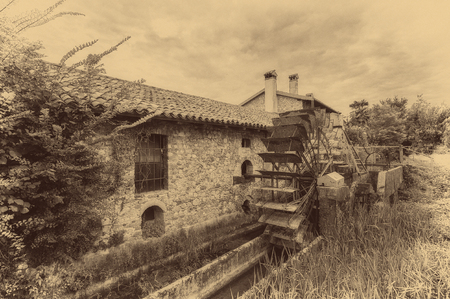 Old water wheels of a watermill. Vintage style picture. Adding grain to give an old photo effect.