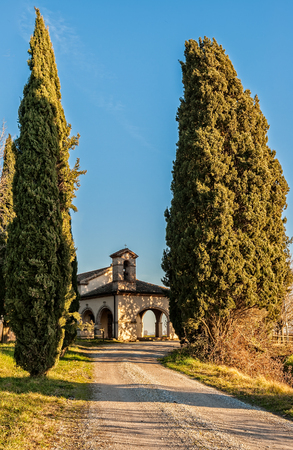 Small 13th century rural church with cypresses. Italy Precenicco.
