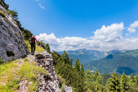 Hiker walks on a mountain trail with wonderful view to admire. Concept of adventure. Healthy lifestyle.