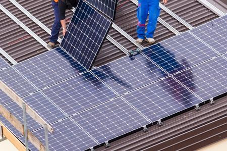 Installation von Sonnenkollektoren auf einem Dach.