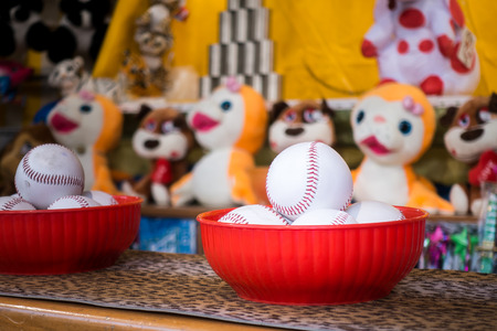 Close-up of baseball balls for the game of throw at jars in a fair. In the background the jars and the prize puppets Zdjęcie Seryjne
