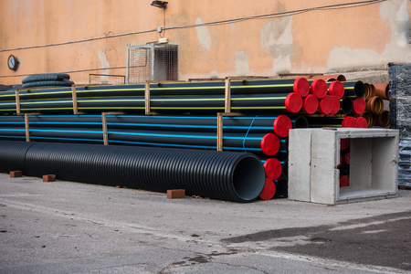 Stack of plastic pipes and prefabricated wells for road works. Stock Photo