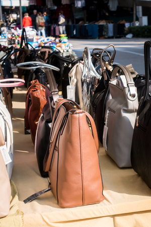 Womens handbags exposed for sale on a stall in the outdoor market. Zdjęcie Seryjne