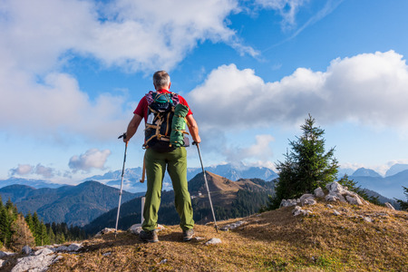 Hiker with backpack is stand on mountain top.