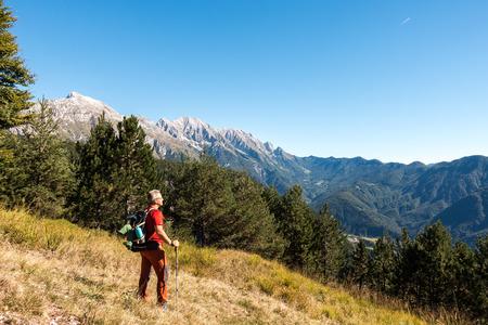 Man hiker is  admiring the range mountains landscape.