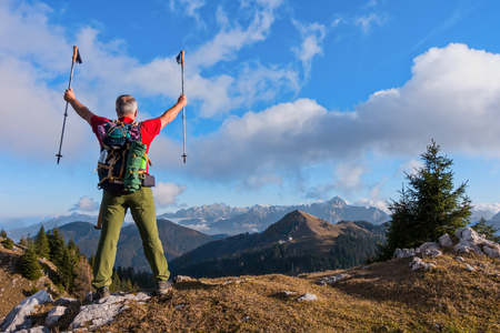Hiker cheering elated and blissful with arms raised in the sky after hiking. Zdjęcie Seryjne